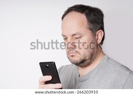middle aged man looking down at his mobile smart phone                               - stock photo