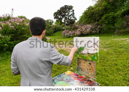 Middle-aged man painter standing in front of  a sketchbook during creation a sketch of his picture on a trestle and easel painting with oils and acrylics in a park - stock photo