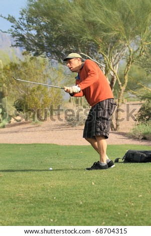 middle-aged man playing golf - stock photo