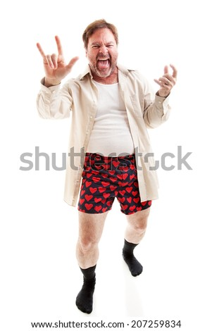 Middle aged man plays air guitar in his underwear and gives the rock-n-roll symbol.  Full body on white.   - stock photo