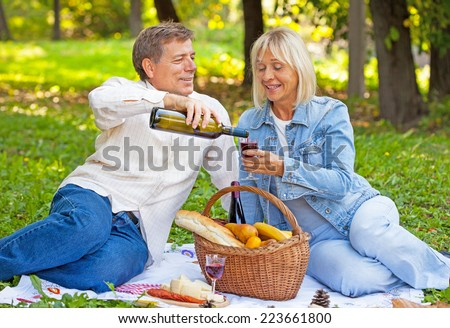 Middle aged man pouring wine to his wife on a picnic in a a countryside