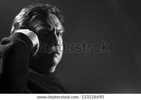 middle-aged man put a finger to his temple - stock photo