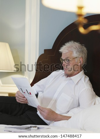Middle aged man reading document in bed