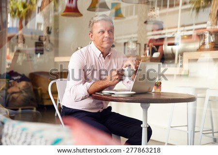 Middle aged man sitting in a cafe - stock photo