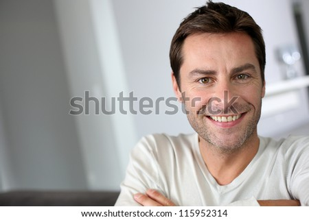 Middle-aged man sitting in sofa with arms crossed - stock photo