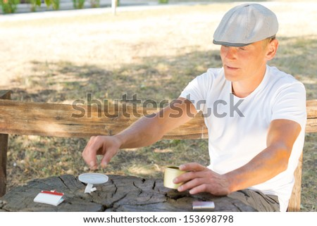 Middle-aged man sitting on a wooden park bench on a hot summer day rolling himself a cigarette from a container of tobacco - stock photo