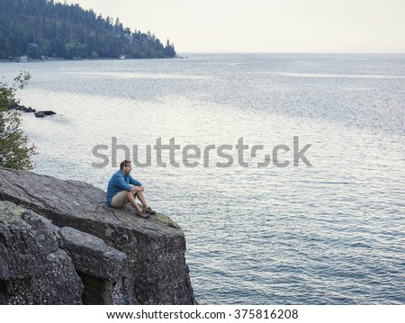 Middle aged man sitting on the edge of cliff overlooking a beautiful ocean bay thinking, meditating and praying - stock photo