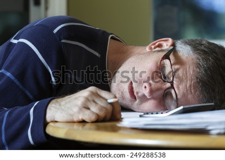 Middle-aged man takes a sleep break while doing paperwork at home.
