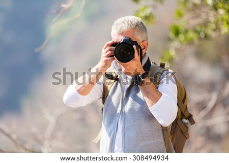 middle aged man taking photos in mountain valley with dslr camera - stock photo