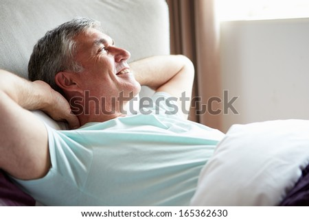 Middle Aged Man Waking Up In Bed - stock photo