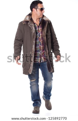 middle aged man walks with winter clothing