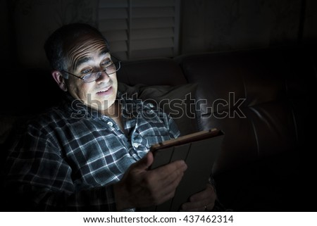 Middle aged man wearing pajamas reading tablet at night in bed looking scared or surprised with copy space - stock photo