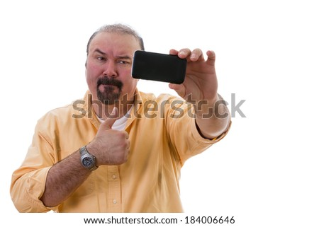 Middle-aged man with a goatee standing posing while taking a self portrait on his mobile as he gives a thumbs up of approval with a frown as though reluctant to do so, isolated on white