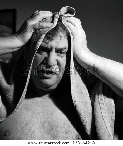 middle-aged man with a towel out of the bathroom - stock photo