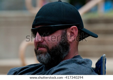 Middle-aged man with black and grey beard wearing sunglasses and hat backwards. - stock photo