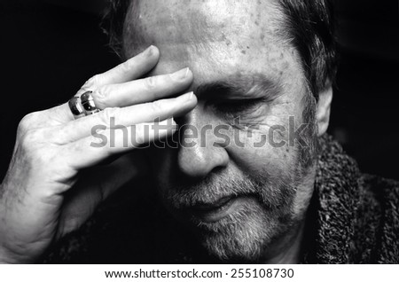 Middle aged man with bristle beard and hand on forehead looking tired, fed up or suffering with insomnia.