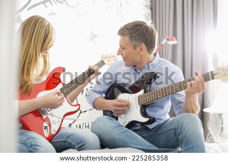 Middle-aged man with daughter playing guitars at home - stock photo