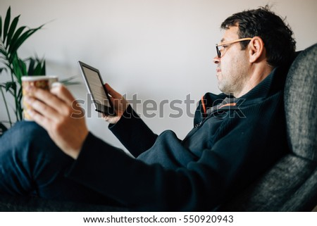 Middle aged man with glasses reading a book ebook at home on armchair