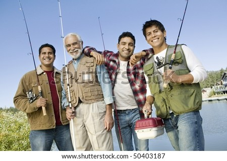 Middle-aged man with three sons holding fishing rods, smiling, (portrait)