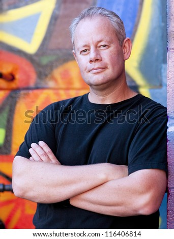Middle aged man with urban graffiti background - stock photo