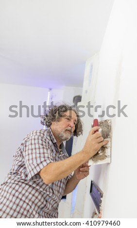 Middle-aged man worker, builder or homeowner plastering a white wall preparing it for painting as he repairs a crack or some other imperfection. - stock photo