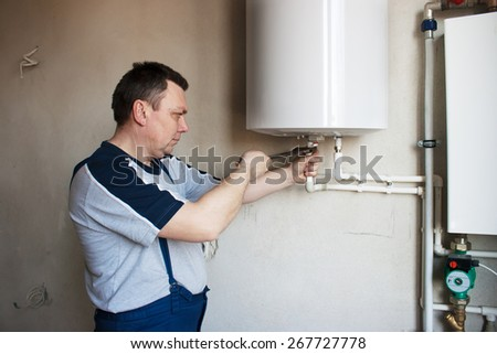 middle-aged man worker in blue trousers and gray t-shirt tightens the screws with a wrench on the boiler in the room of new house