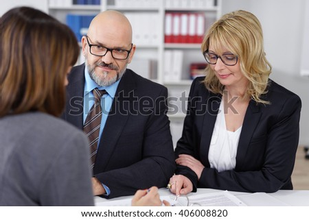 Middle-aged management team in a meeting with a serious businessman and woman listening to a female colleague speaking with thoughtful expressions - stock photo