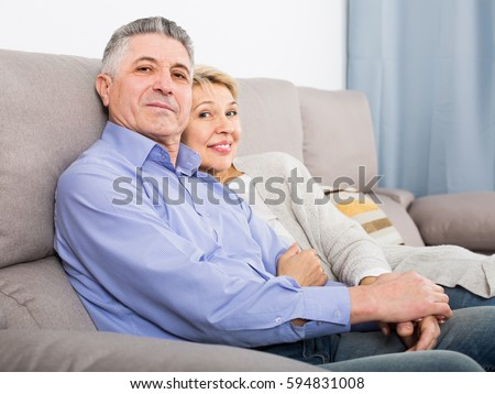 middle-aged married couple in cozy house are warmly reconciled after quarrel