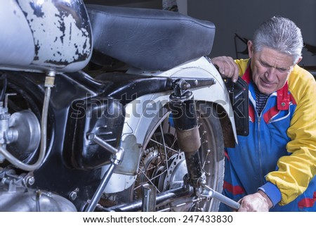 middle aged mechanic is tightening the shock absorber of a classic motorcycle with a wrench in process of restoration at his workshop - focus on the man face