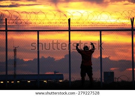 Middle-aged men stand rail, steel mesh and barbed wire at sunset. The concept of restricted freedom of independence. - stock photo