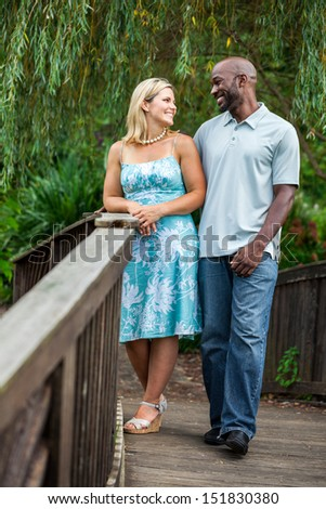 Middle aged mixed race couple on a bridge at the park
