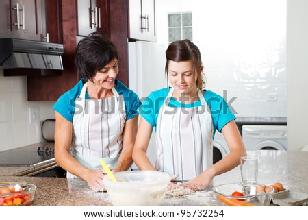 middle aged mother and teen daughter baking in kitchen - stock photo