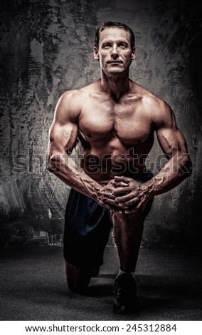 Middle-aged muscular sportsman on his knee - stock photo