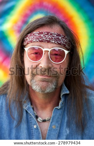 Middle-aged nonconformist man with long brown hair and goatee beard wearing headband, necklace, blue denim shirt and white frame red plastic sunglasses while looking with a peaceful expression - stock photo