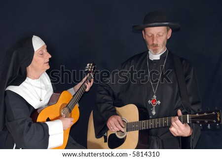 Middle aged nun and priest playing the guitar.  Religion, christianity, lifestyle, entertainment, music, concept - stock photo