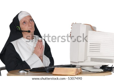 Middle aged nun, sister on computer, connection with god.  Religion, christianity, lifestyle,  communication concept