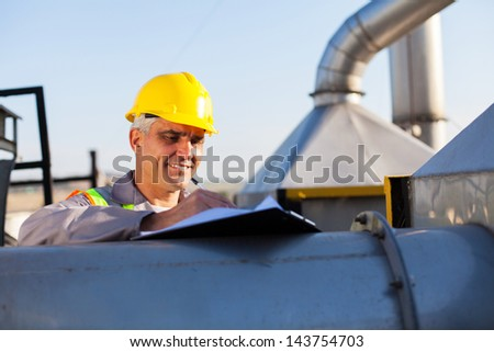 middle aged oil chemical industry technician working outdoors