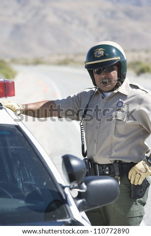 Middle aged police officer standing by his car - stock photo