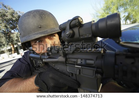Middle aged policeman aiming with gun outdoors