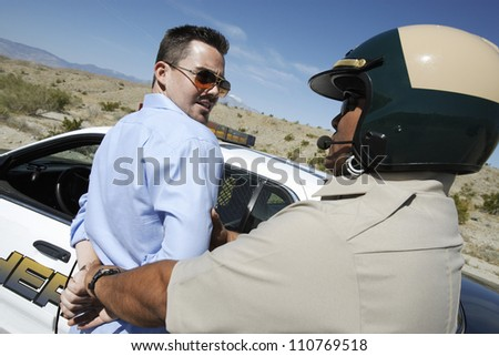 Middle aged policeman arresting a man - stock photo