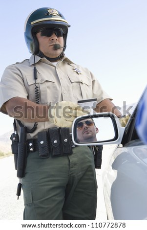 Middle aged policeman checking driving license - stock photo