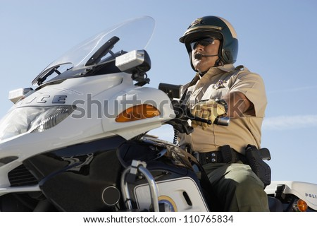 Middle aged policeman riding motorbike from below - stock photo