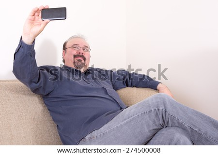 Middle-aged portly man wearing casual dark blue shirt and gray jeans while sitting on the sofa and taking selfie horizontal portrait pictures with a smart mobile phone, with copy space on white wall - stock photo