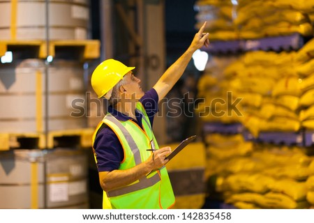 middle aged shipping company worker counting pallets in warehouse before dispatching - stock photo