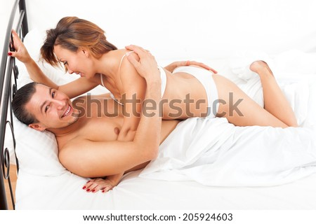 Middle-aged smiling couple kissing and playing on white sheet in bed at home