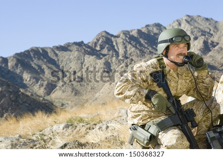 Middle aged soldier using telephone while holding rifle against mountain