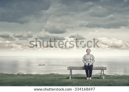 Middle aged stout woman sitting on bench