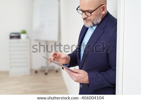 Middle-aged stylish businessman checking information on his tablet as he stands leaning against a wall in the office - stock photo