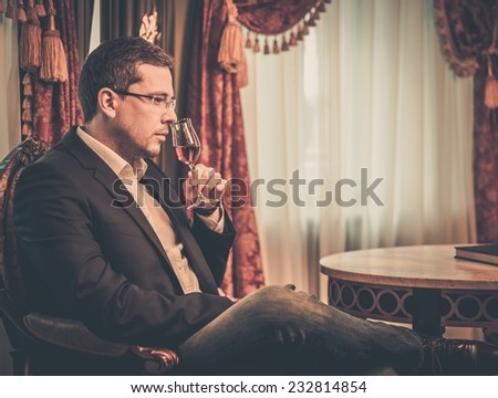 Middle-aged tasting cognac in luxury vintage style interior  - stock photo