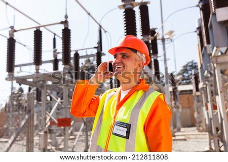 middle aged technician talking on cell phone in substation - stock photo